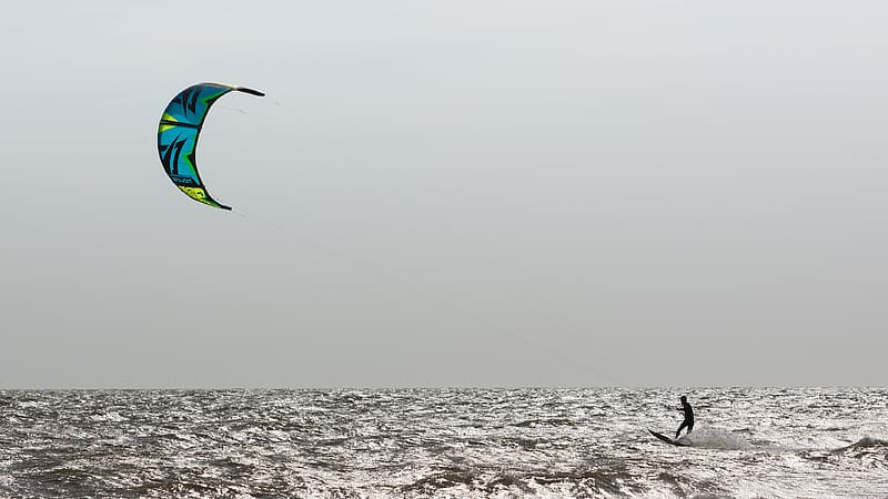 Person in green and blue parachute over the sea