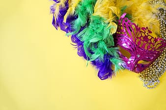 Multicolored party mask on yellow surface