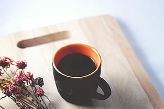 Black and orange ceramic mug on top of brown wooden chopping board
