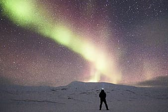 Man standing on middle of snow-covered field with Aurora Borealis in background