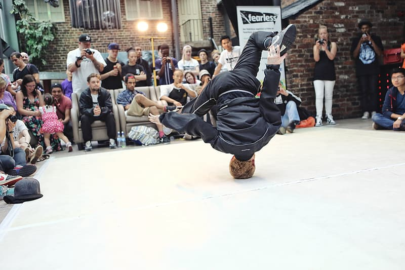 Man wearing black jacket and pants doing head stand