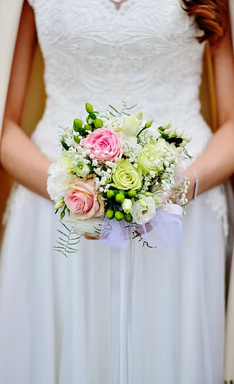 Bride holding pink, white, and green roses bouquet