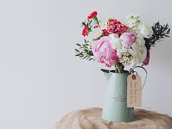 Red, pink, and white peonies and carnations centerpiece in teal metal watering can
