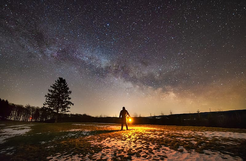 Silhouette of person standing on pathway under starry night