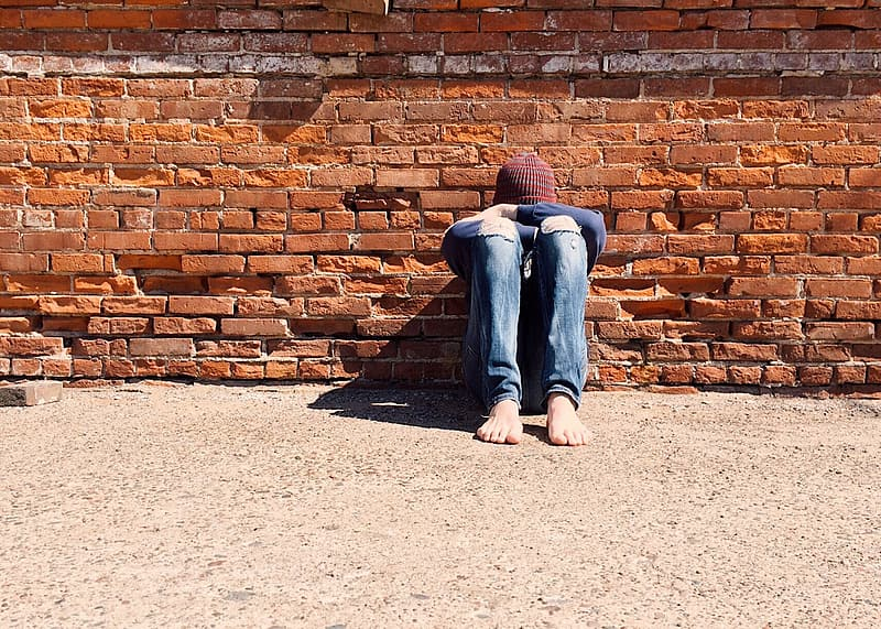 Person sitting and leaning on brown concrete wall at daytime