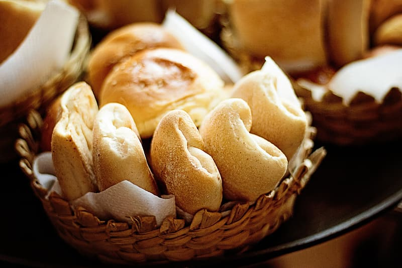 Baked breads in round brown wicker bowl