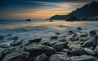 Rocky shore with sea waves crashing on shore during sunset