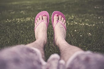 Person in pink flip flops standing on green grass field during daytime