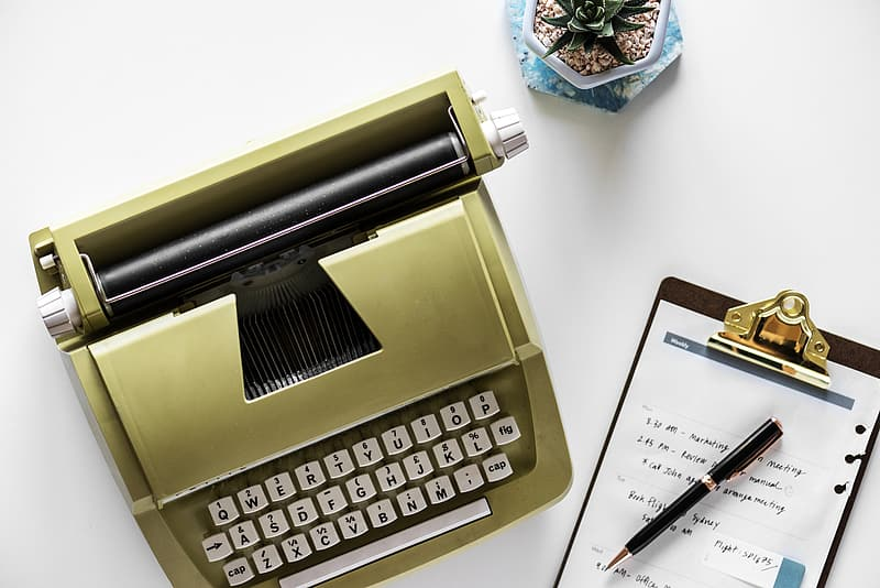 Brown typewriter beside clipboard on white surface