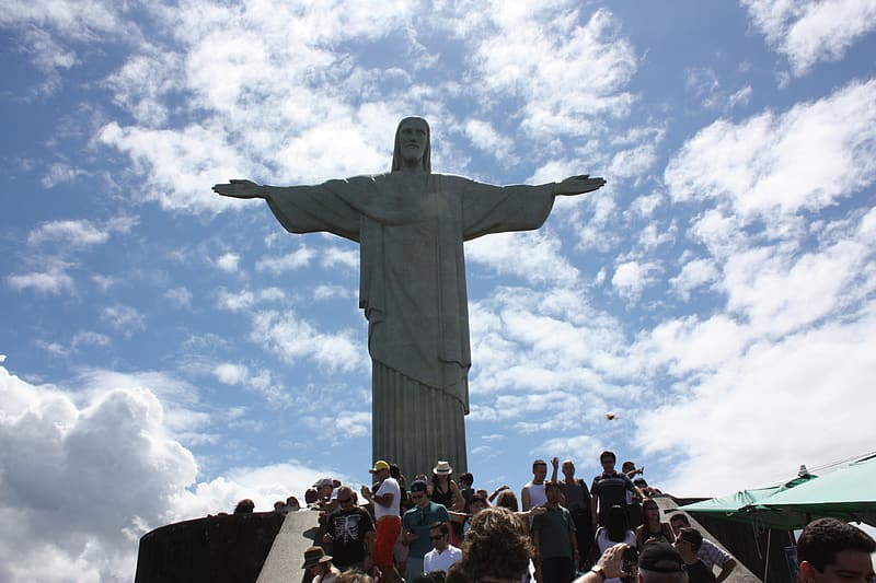 People standing near statue under white clouds and blue sky during daytime