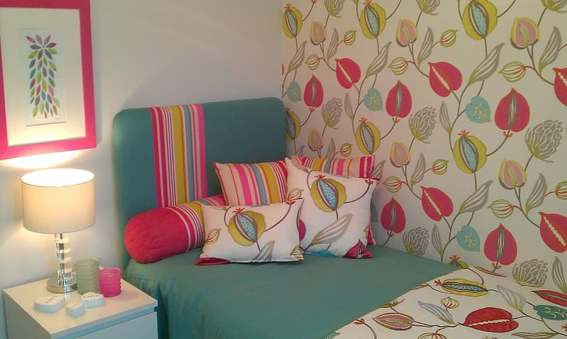 Pillows on bed beside turned on table lamp