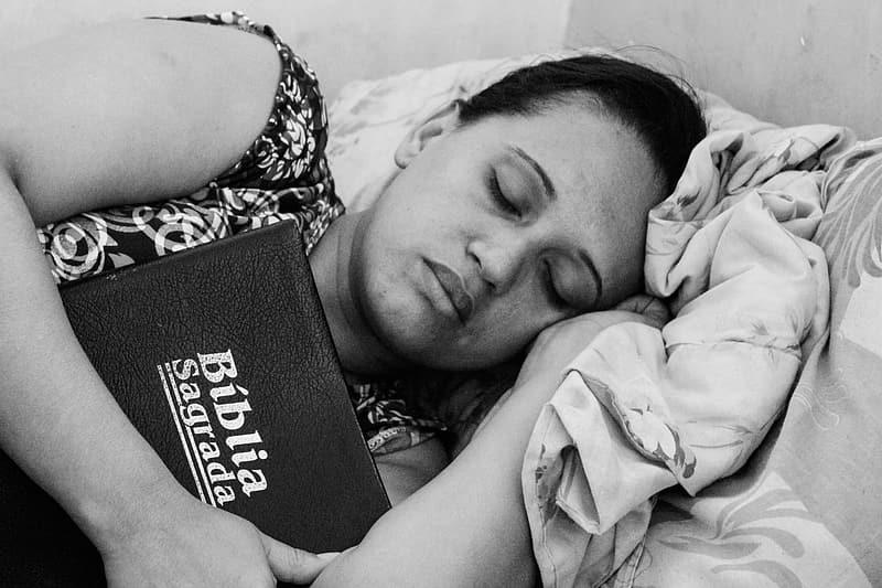 Woman sleeping while holding a bible