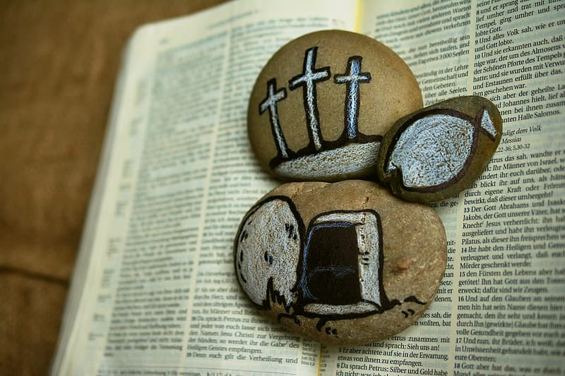 Three stones with paint on top of bible
