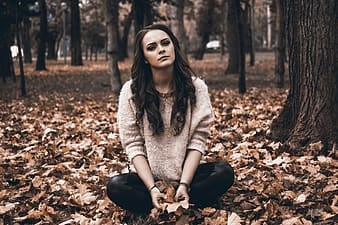 Woman in gray sweater and black pants sitting on ground full of leaves