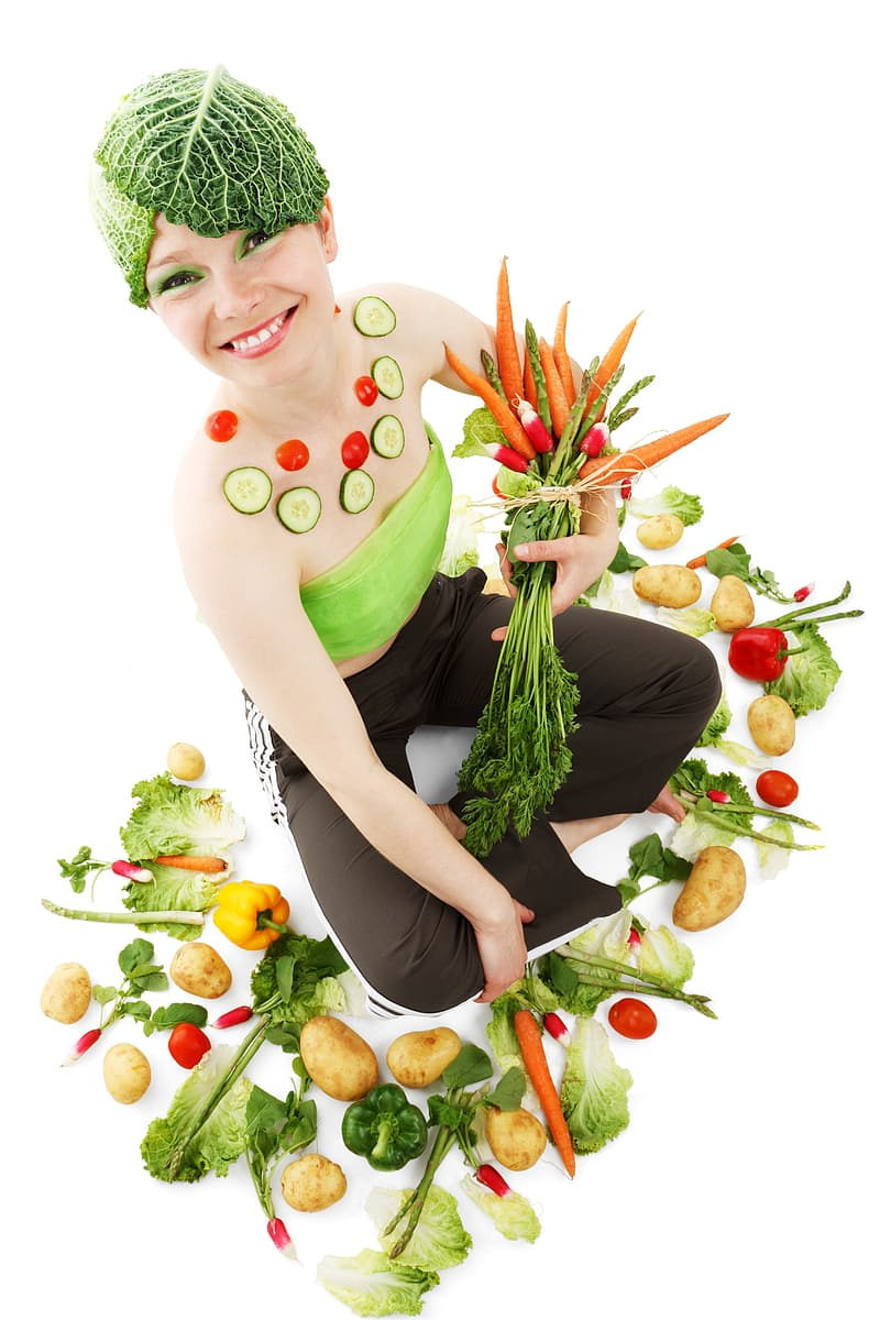 Woman in green bondeau and black pants while holding bunch of carrots