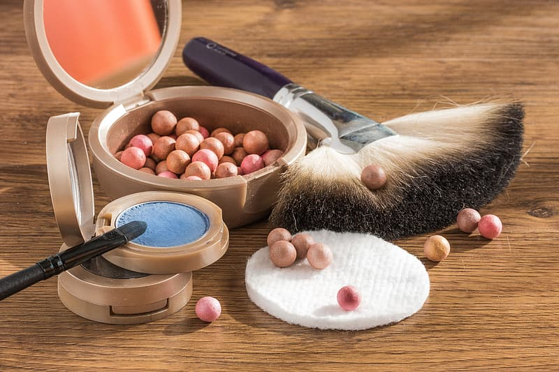 Assorted makeup kits on brown wooden table