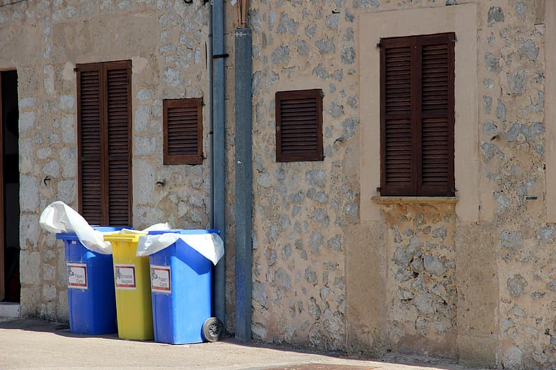 Three blue and yellow trash bins beside beige stone building at daytime