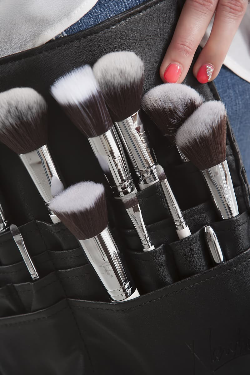 Person touching case with makeup brushes