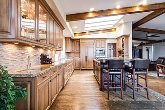 Photo of brown wooden kitchen cupboards near kitchen island