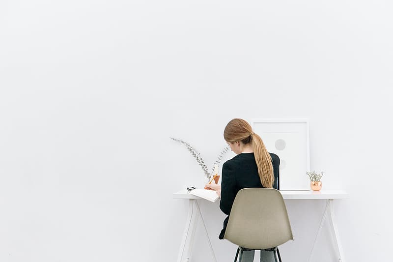 Woman wearing black long-sleeved shirt sitting on chair writing on white book