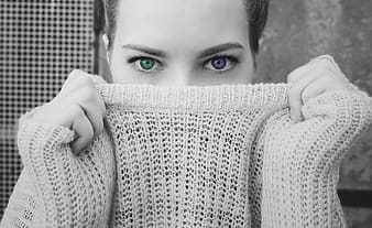 Selective-color photography of woman covering mouth with sweater