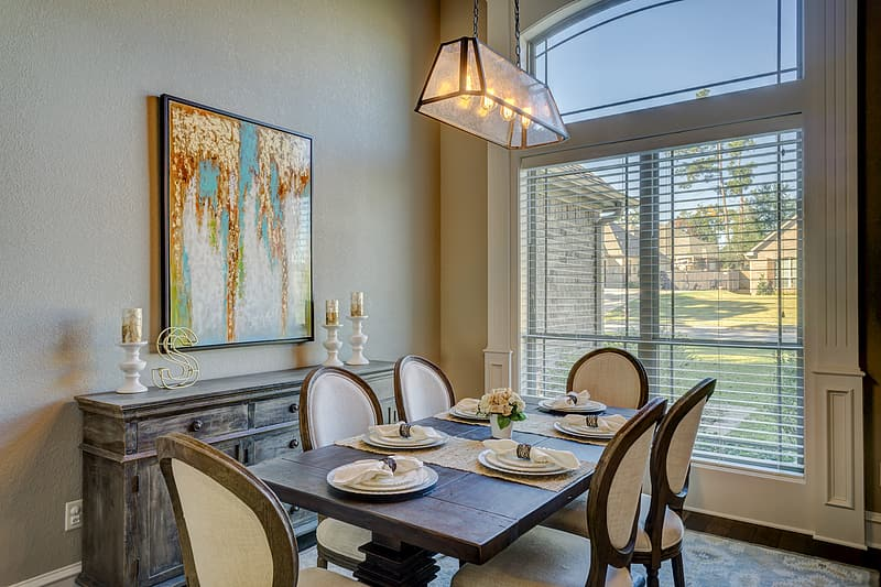Brown wooden table and white chairs with  white window blinds french window type frame