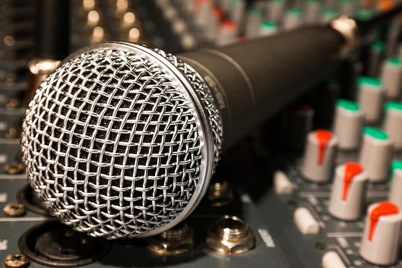 Black and gray corded microphone on audio mixer