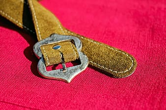 Brown leather belt on pink textile