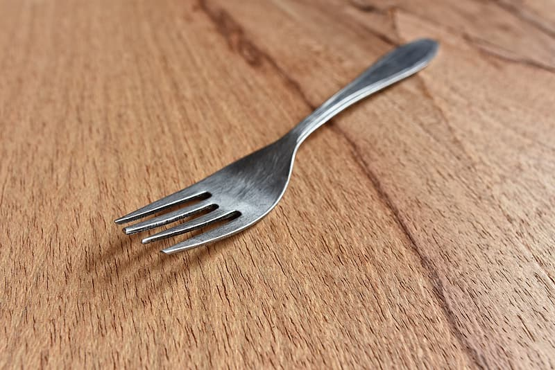 Silver fork on brown wooden table