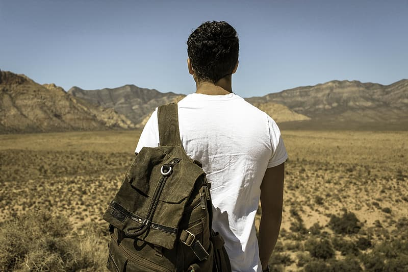 Man in white shirt carrying backpack standing in front of mountain
