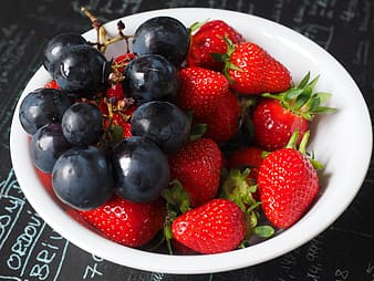 Strawberries with grapes in white ceramic bowl