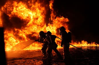 Silhouette of three firefighters surrounded by fire