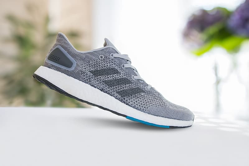 Selective focus photography of unpaired grey and white adidas shoe on white surface