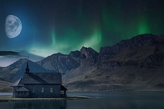 Brown wooden house on lake near snow covered mountain during night time