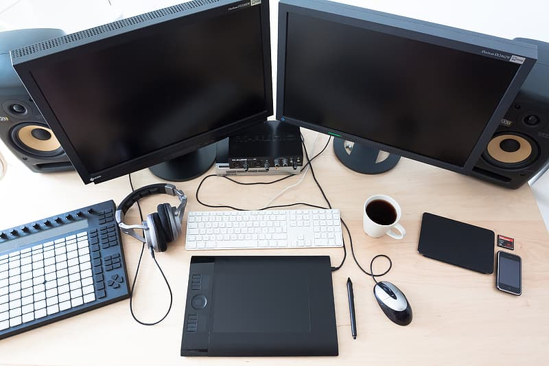 Two black flat screen computer monitor on brown wooden table