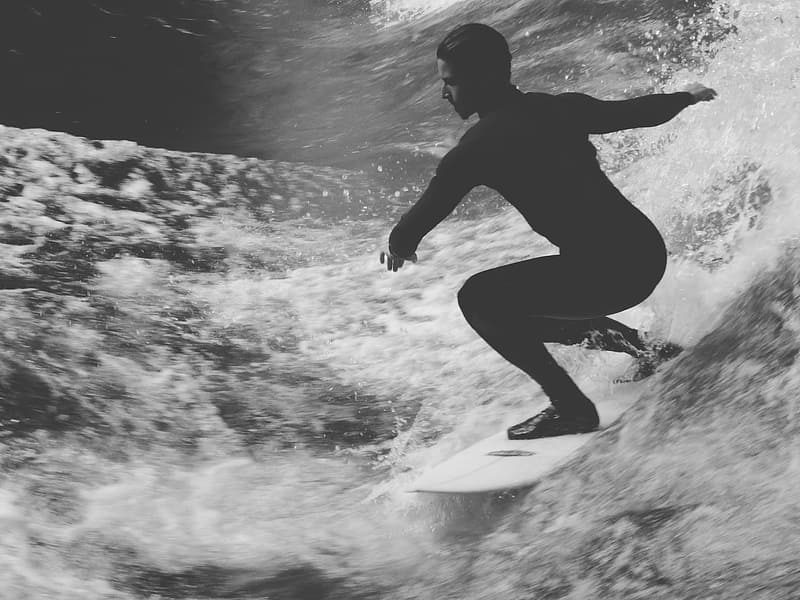 Grayscale photo of man riding surfing board