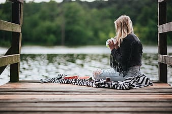 Woman in black leather jacket and white and black pants sitting on brown wooden dock during