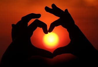 Silhouette photo of person's hand making heart