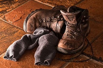 Pair of brown leather boots and gray socks on brown tiles