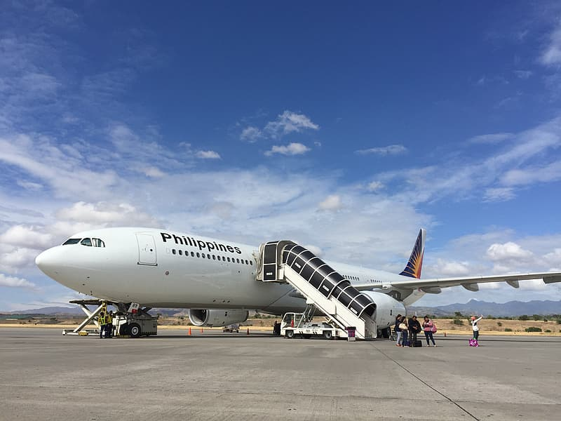White and black Philippine Airline airplane on runway