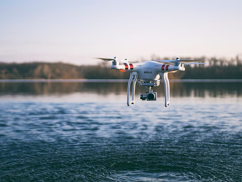 Red and white DJI Phantom 3 flying over body of water during daytime