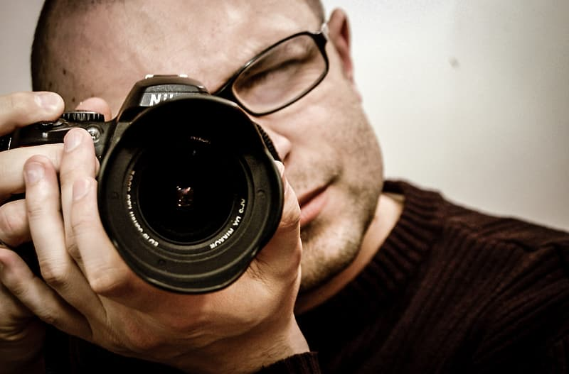 Man in black framed eyeglasses using black Nikon DSLR camera
