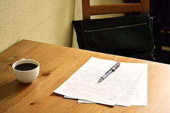 Gray pen on top of white papers and ceramic coffee on top of table