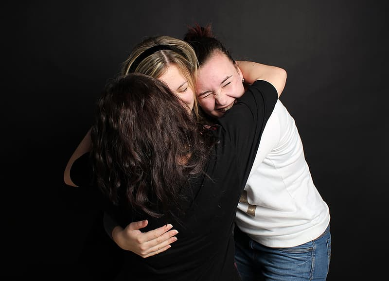 Three women hugging each other photo