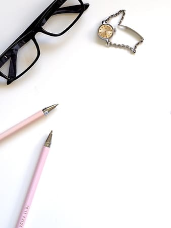 Two pink ball-point pens near black framed eyeglasses on white surface