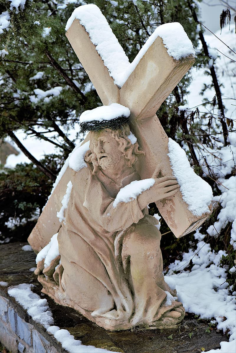 Jesus carrying cross statuette at daytime