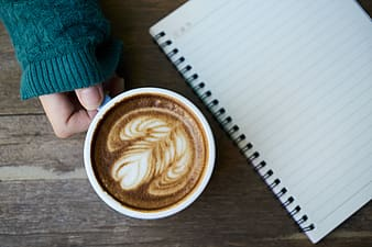 Cappuccino beside spring notebook