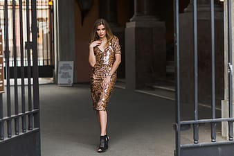 Woman in brown glittered bodycon dress standing near black metal gate during daytime