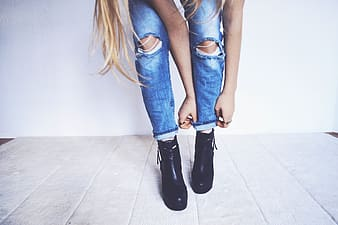 Woman wearing blue distressed jeans and pair of black leather boots