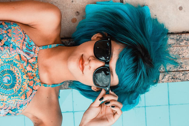 Blue haired woman wearing black framed sunglasses